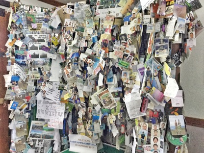 A wall full of mementos from hikers (mostly pictures) in the corner of DENR registration office
